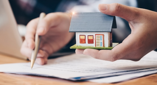 A hand holding a toy house whilst signing a house loan